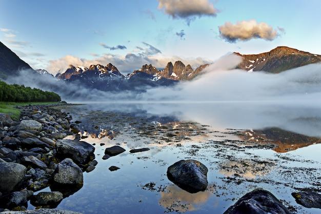 Colpo mozzafiato del mare a specchio che riflette la bellezza del cielo a lofoten, norvegia Foto Gratuite