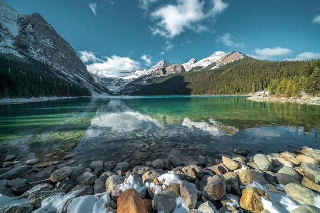 백그라운드에서 호수와 언덕의 청록색 물 아래 아름다운 돌의 숨막히는 샷 무료 사진