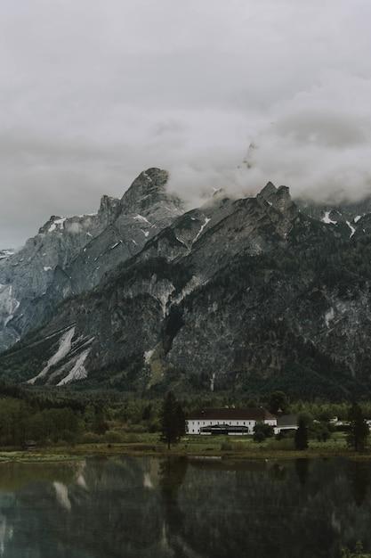 曇り空の下で湖と山の近くの茶色と白の家の息を呑むようなショット 無料写真