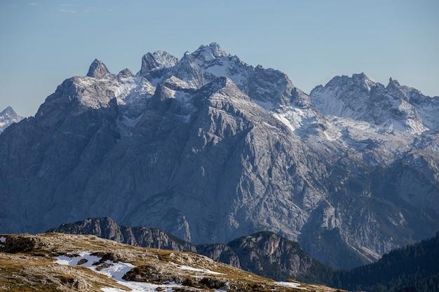 Colpo mozzafiato di rocce innevate nelle alpi italiane sotto il cielo luminoso Foto Gratuite