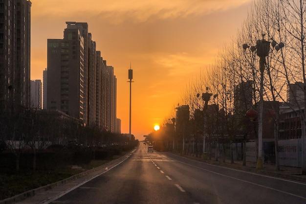 Scatto mozzafiato di un tramonto lungo la strada nel mezzo di una città moderna Foto Gratuite