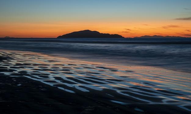 ニュージーランド北島のカピティ海岸にある大滝ビーチでの息を呑むような夕日 無料写真