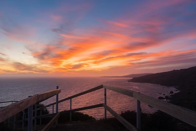 Захватывающий закат над спокойным океаном в окружении холмов Бесплатные Фотографии