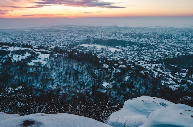 Breathtaking sunset scenery over the city covered with snow in winter Free Photo