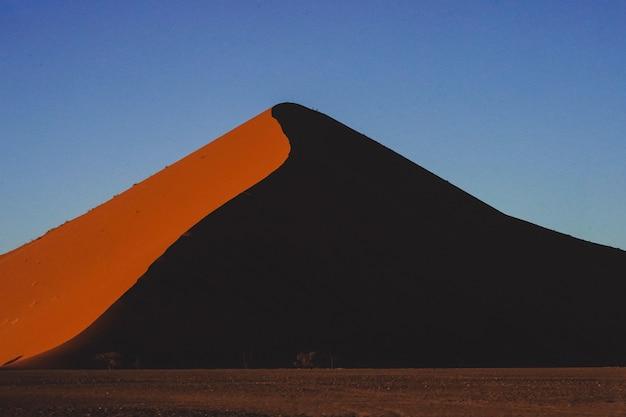 Захватывающий вид на прекрасную песчаную дюну под голубым небом в намибии, африке Бесплатные Фотографии