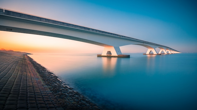 オランダ、ゼーラントブリッジで撮影された静かな川に架かる橋の息をのむような眺め 無料写真
