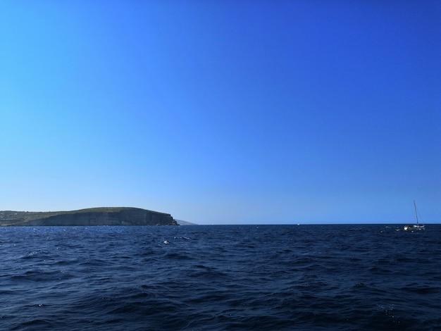 Захватывающий вид на волнистое море на мальте в солнечный день с красивым горизонтом. Бесплатные Фотографии