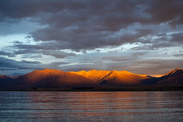 雄大な山脈の背景に反射する海の息を呑むような景色 無料写真
