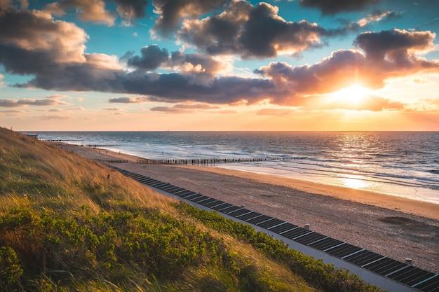 Захватывающий вид на пляж и океан под красивым небом в домбурге, нидерланды. Бесплатные Фотографии