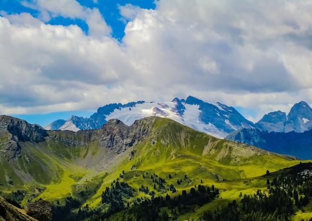 Захватывающий вид на красивые травянистые поля и горы под облаками в небе Бесплатные Фотографии