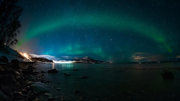 오로라와 함께 매혹적인 하늘 아래 호수와 산의 숨막히는 전망 무료 사진