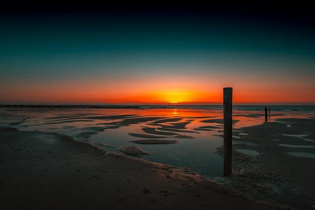 Захватывающий вид на отражение заката в океане в домбурге, нидерланды Бесплатные Фотографии