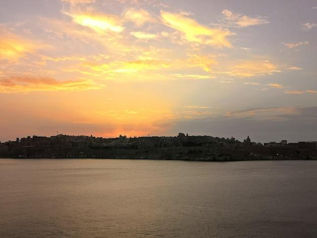マルタの木々に囲まれたビーチの夕日の息を呑むような景色 無料写真