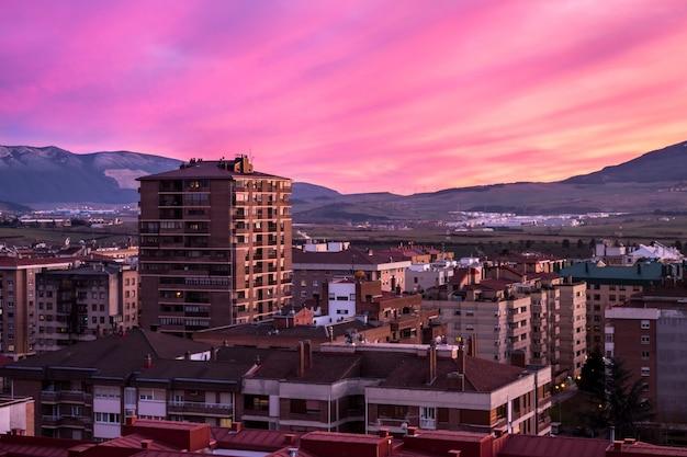 Vista mozzafiato di un tramonto rosa e della città Foto Gratuite