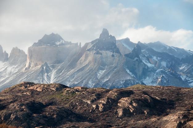 Vista mozzafiato delle montagne innevate sotto il cielo nuvoloso in patagonia, cile Foto Gratuite