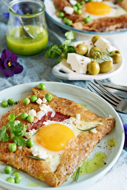 Premium Photo Breton Traditional Pancake Made From Buckwheat Flour With Ham Cheese Egg Feta Green Peas And Green Butter