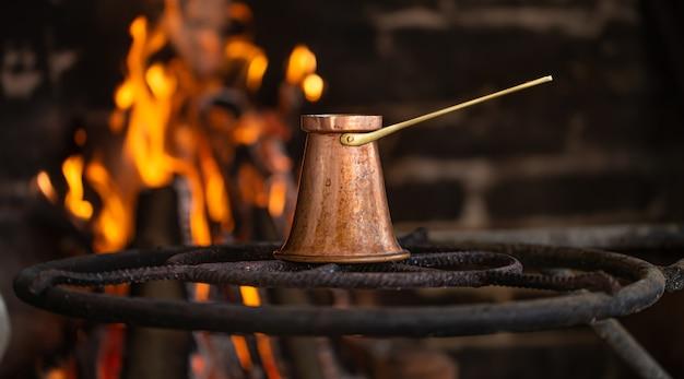 Заварить кофе в турке на открытом огне. концепция уютной атмосферы и напитков. Бесплатные Фотографии
