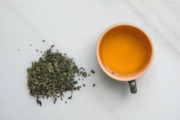 Brewed green tea in ceramic cup. loose leaves scattered on white marble stone background. Premium Photo
