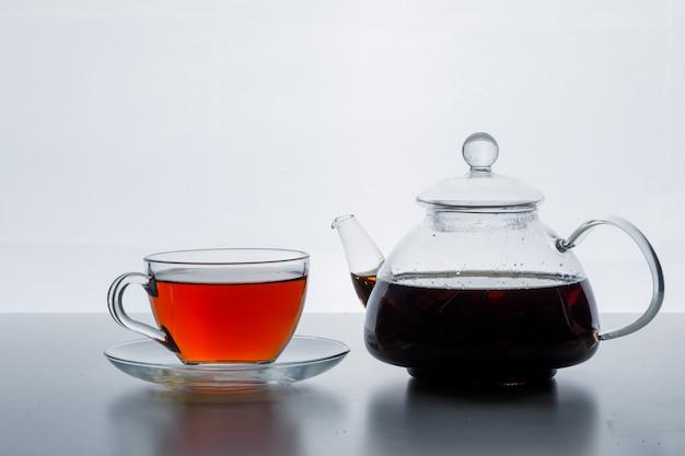 Заваренный чай в чайнике и чашке на белом фоне Бесплатные Фотографии