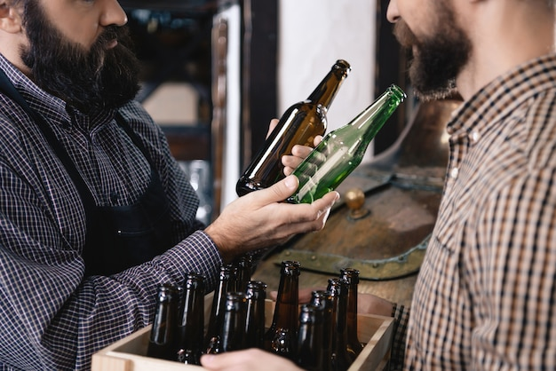 Brewer choosing beer bottle brown and green glass. Premium Photo