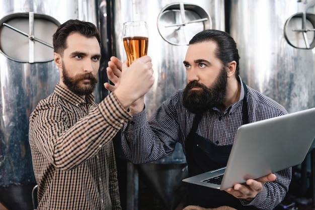 Brewers monitoring beer quality holding glass. Premium Photo
