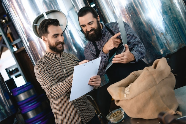 Brewers with laptop and clipboard at microbrewery. Premium Photo