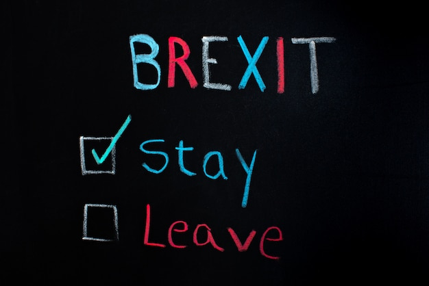 Brexit concept, choice between staying or leaving, written on blackboard. Premium Photo