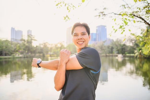 Бегун человек делает упражнения на растяжку плеча, разминка brfore работает в парке Premium Фотографии