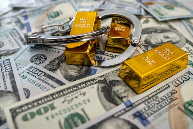 Bribe concept gold bars and handcuff in dollar bills Premium Photo