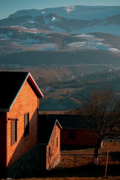 Casa di mattoni attraverso montagne innevate Foto Gratuite