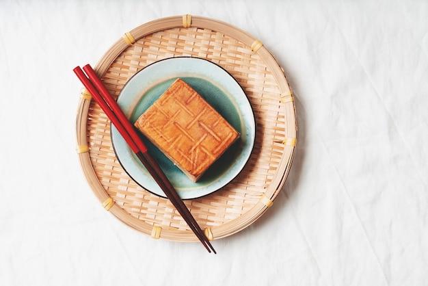 有機燻製豆腐チーズのレンガを竹マットの上に青いプレートで添えました。フラットレイ。上面図。ビーガンスナックのコンセプト Premium写真