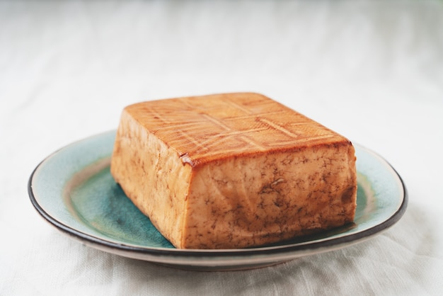 有機燻製豆腐チーズのレンガを竹マットの上に青いプレートで添えました。ビーガンスナックのコンセプト Premium写真