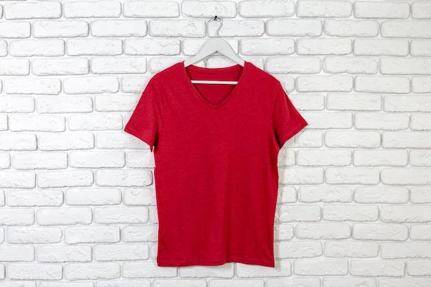 Brick whitewashed wall with t-shirt on hanger Premium Photo