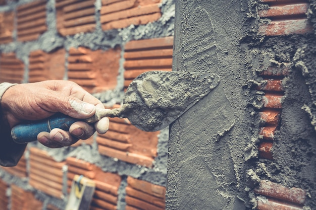 Bricklaying. construction worker building a brick wall. Free Photo
