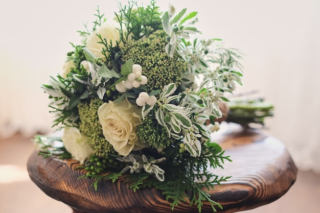 Bridal bouquet. wedding. wedding bouquet of white and green flowers stands on a chair Premium Photo