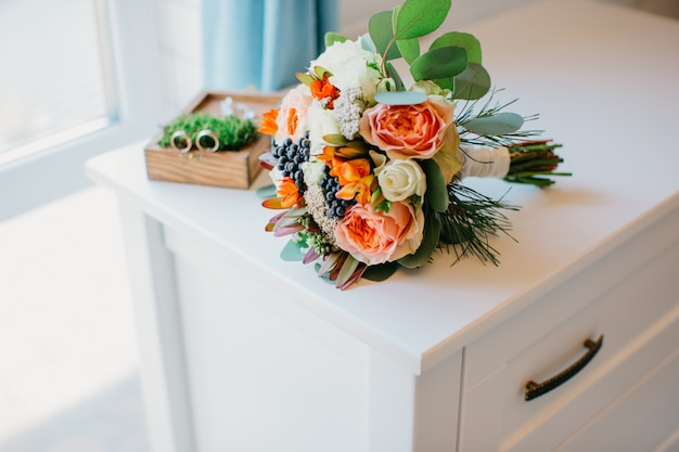 Bridal bouquet of white and orange flowers on a white table. Premium Photo