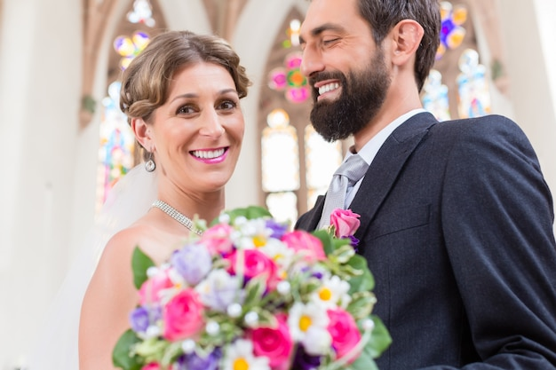Bridal couple in church with flower bouquet Premium Photo