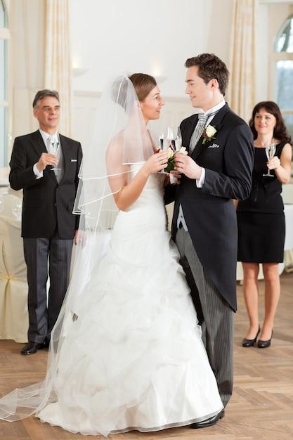 Bridal couple clinking glasses Premium Photo
