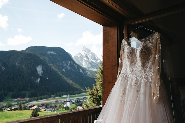 Bridal dress hangs on a hanger on a window with a mountains view Free Photo
