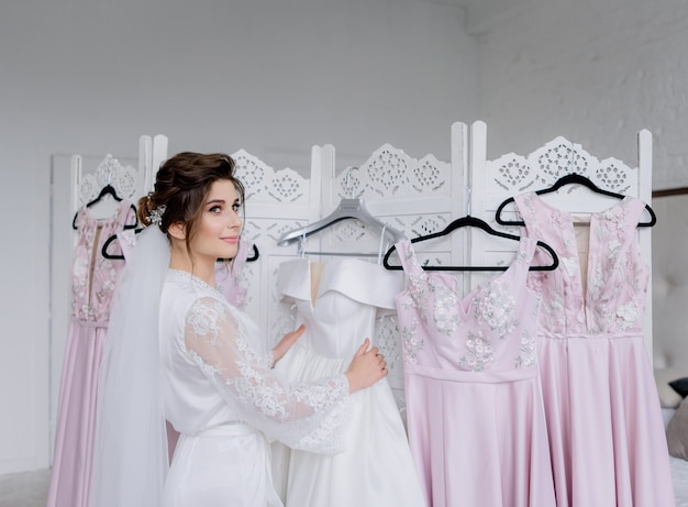 Bridal morning, beautiful bride is dressing up for the wedding ceremony, wedding dresses Free Photo