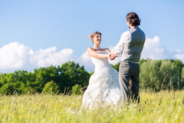 Bridal pair dancing on field celebrating Premium Photo
