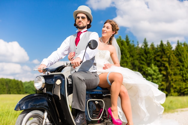 Bridal pair driving motor scooter wearing gown and suit Premium Photo