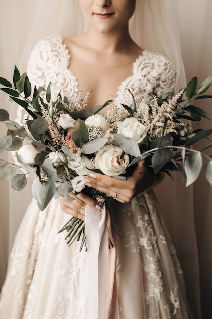 Bride in an amazing bridal dress with a beautiful bouquet Free Photo