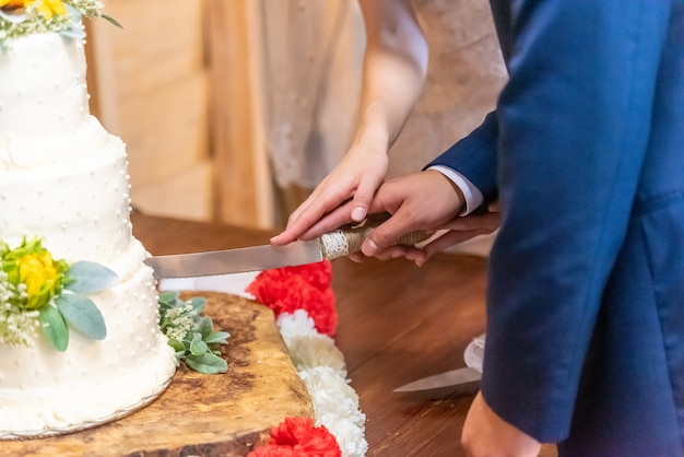 신부와 신랑 아름다운 하얀 웨딩 케이크를 절단 무료 사진