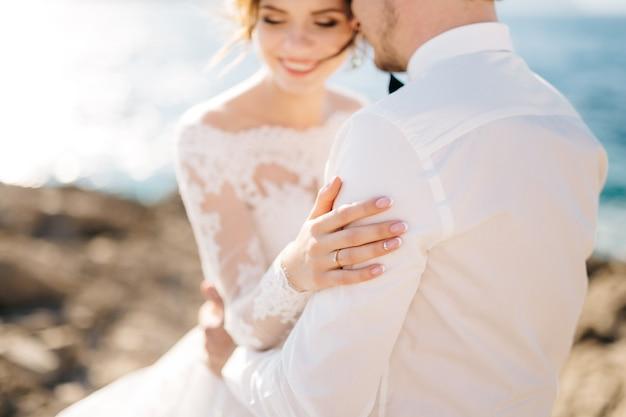 Жених и невеста обнимаются на каменистом пляже острова мамула Premium Фотографии