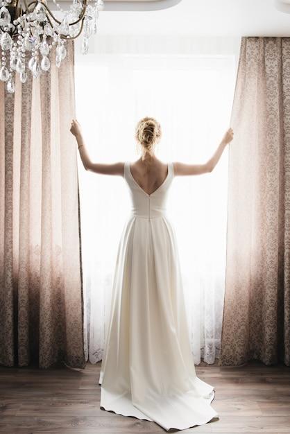 新郎新婦が外を見る窓に立っています。 Premium写真
