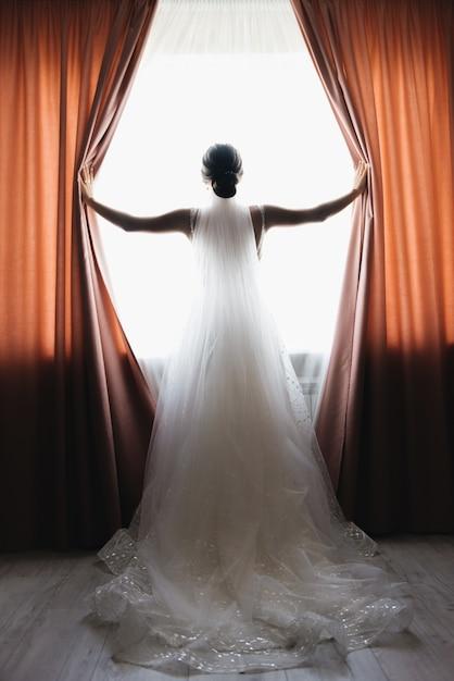 新郎新婦は外を見て窓に立っています。 Premium写真