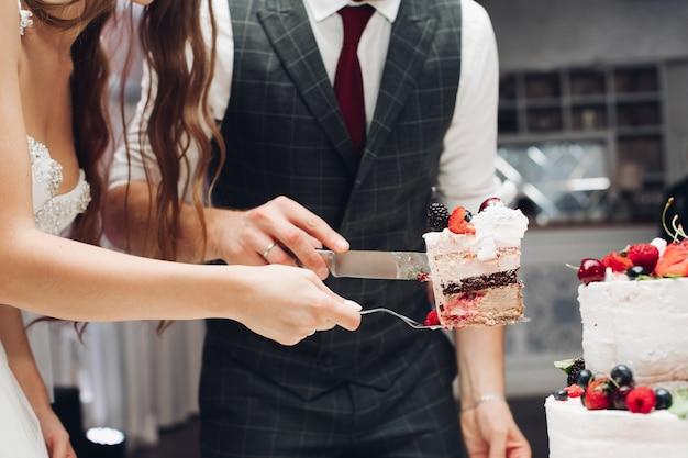 Жених и невеста режут свадебный торт Premium Фотографии