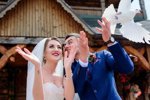 Жених и невеста держат голубей, стоящих перед деревянной церковью Premium Фотографии