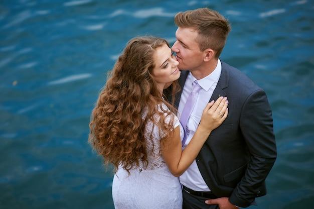 Жених и невеста возле озера в день свадьбы. Premium Фотографии